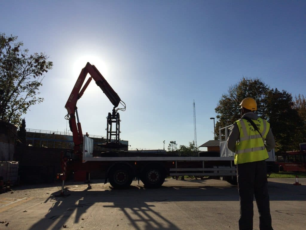 Man standing looking at lorry loader